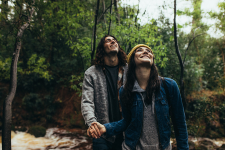 Young woman with her boyfriend in a forest, both looking up and smiling. Happy young couple standing together on rainy day at the forest.