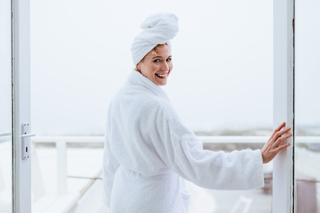 Smiling woman in a bathrobe with a towel wrapped on head. Rear view of a woman standing in balcony after her bath.