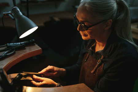 Goldsmith working and shaping an unfinished jewelry piece with a tool at a workbench in workshop. Mature female goldsmith working in her workshop. Stockfoto