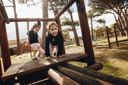 Two little girls playing at playground outdoors. Twin sisters enjoying playing on wooden structure at park.