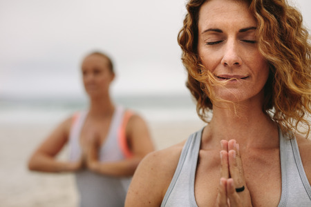 Close up of a woman with closed eyes practicing yoga at the beach. Women in fitness wear at the beach doing yoga with closed eyes and joined palms.