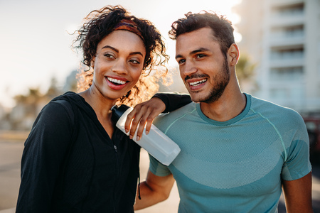 Couple in fitness wear relaxing outdoors in the morning. Smiling couple standing together taking a break after work out.