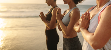 Three women standing on the beach practicing meditation and yoga with sea and sun flare in the background. Women doing yoga standing at the sea shore with joined hands. Foto de archivo - 113598483