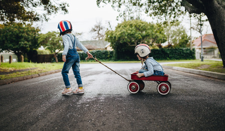 Little girl wearing helmet pulling her sister sitting in a wagon cart on the road. Kids playing outdoors with toy trolley. Archivio Fotografico
