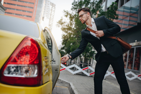 Entrepreneur opening the door of a taxi standing on the pavement. Man taking a taxi to go to office.