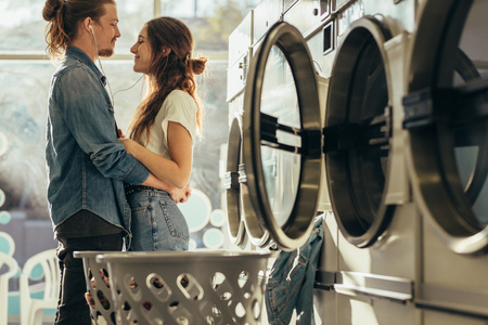 Happy couple sharing earphones listening to music standing in a laundry room. Couple in love standing facing each other with closed eyes. Stock Photo