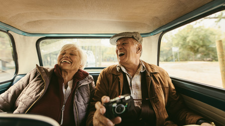 Cheerful old couple sitting on backseat of their car and laughing. Senior man and woman enjoying traveling together by a old car.