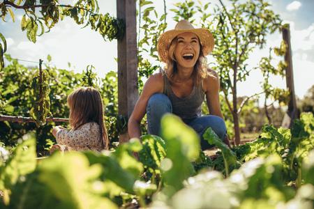 Schöne junge Bäuerin, die in ihrem Garten mit ihrer Tochter sitzt. Junge Mutter und Tochter, die auf dem Bauernhof arbeiten. Standard-Bild