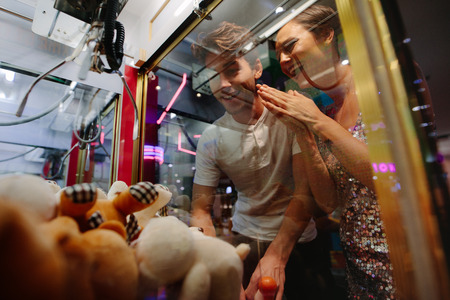 Happy couple having fun playing coin operated games at a gaming parlour. Man playing game at a gaming arcade while his girl friend cheers him.