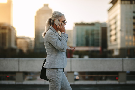 Side view of mature woman in business suit walking back to home talking on phone. Senior businesswoman using cellphone on city street with urban background.