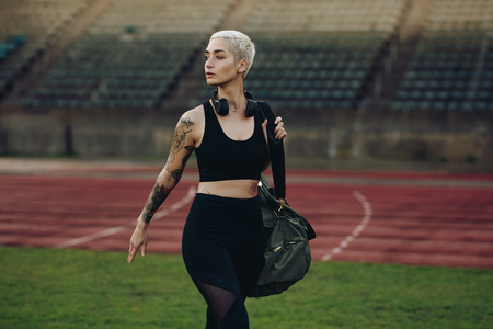 Female runner walking in a track and field stadium carrying her bag. Woman in fitness wear walking in a stadium looking back.