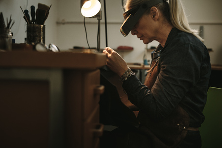 Side view of senior woman wearing magnifying glasses sitting at her workbench and examining the product while making process. Mature female jeweler working on new jewelry products.