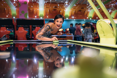 Happy woman playing the air hockey game at a gaming arcade. Woman at a gaming parlour playing coin operated air hockey game.