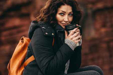 Traveler woman having hot coffee and looking at camera. Female hiker resting with a coffee.