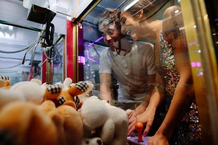 Happy couple playing games at a gaming arcade. Man and woman having fun at a gaming parlour playing coin operated games.