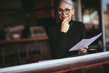 Businesswoman sitting at a coffee table with some documents. Senior woman doing her work sitting at a coffee shop.