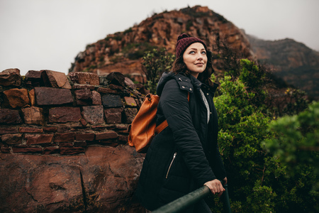 Portrait of attractive woman standing by a railing at hill top and looking away. Woman relaxing on vacation at mountain top.