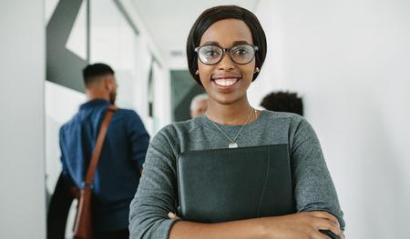 Portret van een vrolijke Afrikaanse zakenvrouw met een bril die op kantoor staat met een team op de achtergrond. Glimlachende vrouwelijke executive met map in kantoor hal met collega's praten aan de achterkant.