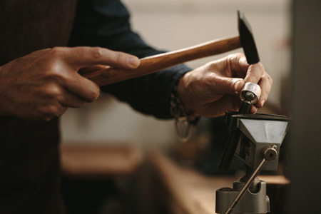 Close up of senior female jeweler making a silver ring using tools. Jewelry designer shaping a ring at her workshop.