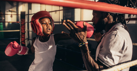 Trainer teaching a kid how to hit punches. Kid wearing boxing gloves and head guard training with his coach inside a boxing ring.