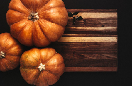 Top view of pumpkins on wooden board over black background. Halloween flat lay concept design.