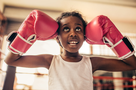 Kid wearing boxing gloves standing in a boxing ring touching her head with gloves and looking up.