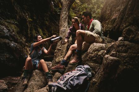 Woman serving coffee to female friend sitting on rocks. Friends taking coffee break while hiking in rocky mountain. 写真素材
