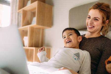 Little boy with mother having great time at home. Smiling woman and son with laptop on bed.