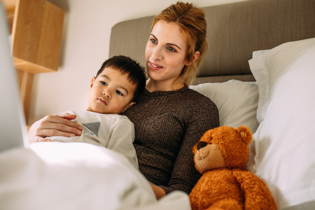 Beautiful mother with her cute son resting on the bed watching something interesting on laptop. Innocent boy with mother looking at laptop with a teddy bear at the side.