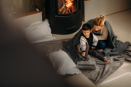 Young family sitting near fireplace looking at laptop. Son pointing at laptop to show something interesting to his mother at home.