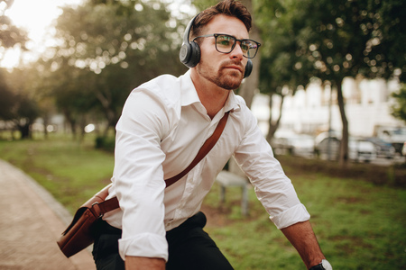 Man commuting to office on a bicycle early in the morning. Man wearing office bag and wireless earphones riding a bicycle. Stockfoto