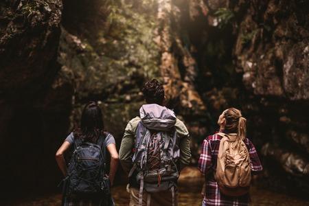 Vista posteriore di tre giovani amici con zaino che guardano lontano a Mountain View. Gruppo di giovani che fanno un'escursione nella natura guardando una vista.