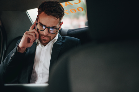 Businessman doing office work while commuting to office in a taxi. Entrepreneur managing business work on the move sitting in a car.