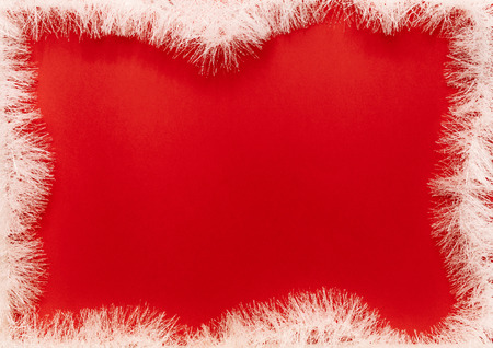 White fir garland frame on red background. Christmas frame with fir garland. Copy space in center for your text.