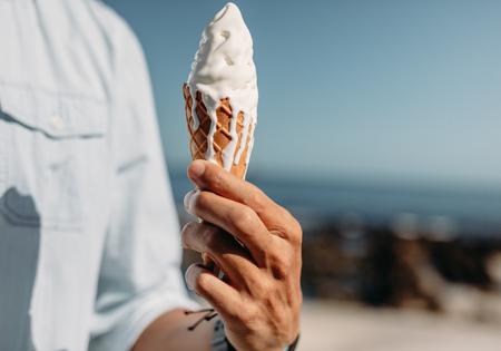 Cerca de la mano del hombre que sostiene un cono de helado de fusión. Hombre que sostiene un helado en un día soleado.