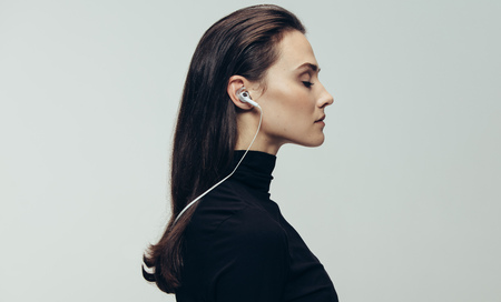 Side view of woman in black dress wearing earphones with eyes closed. Woman wearing earphones against grey background.