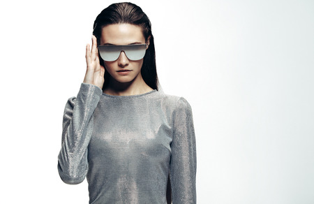 Trendy fashion portrait of woman wearing silver outfit and mirrored stylish sunglasses. Futuristic female model posing in studio.