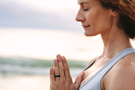 Side view of a fitness woman standing at the beach meditating with closed eyes and joined palms. Close up of a woman practicing yoga and meditation outdoors. Foto de archivo - 113597339