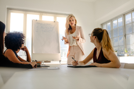 Female manager discussing over budget and income with colleagues during a board meeting. Group of businesswomen having meeting over finance.