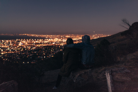 Couple watching the brightly lit city sitting on top of a hill late in the evening. Rear view of couple sitting together on a hill talking and enjoying the city view at night. Фото со стока