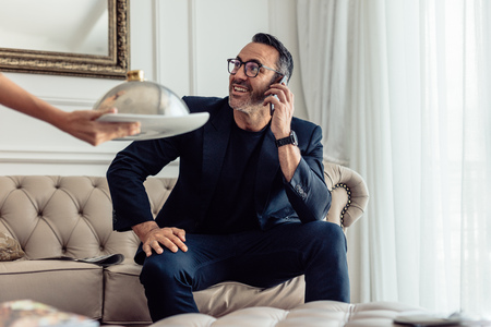 Mature businessman sitting on sofa talking on mobile phone in hotel room with a waiter serving food. Room service waiter serving food to a businessman talking on cellphone. Imagens