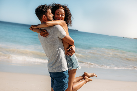 Happy woman hugging her boyfriend at the beach with her feet off the ground. Man lifting his girlfriend above the ground hugging her on the beach with sea in the background.