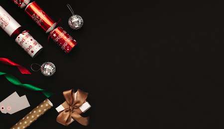 Christmas decoration flat lay on black background. Directly above shot of christmas crackers, mirror balls, colorful ribbons, tags and gift box with copy space.
