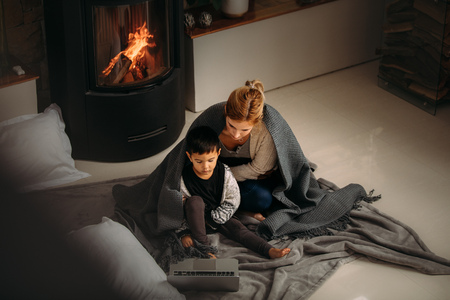 Woman and a little boy with blanket sitting on floor looking at  laptop. Mother and son watching cartoons on laptop sitting near fireplace at home. Stock Photo