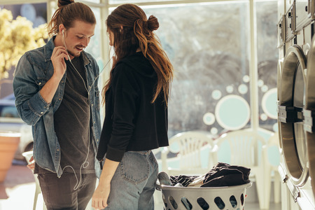 Shy couple standing in the laundry room facing each other listening to music. Man and woman listening to music sharing earphones standing together in laundry room.