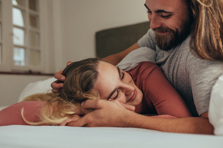 Smiling woman with eyes closed enjoying the love and care of her husband. Smiling man lying on bed with his wife holding hands and loving her.