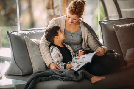 Happy mother and son sitting on couch with a story book living room. Woman and little boy with picture book at home.