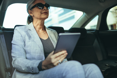 Female entrepreneur travelling to office in a luxurious car sitting on backseat with digital tablet. Senior businesswoman in car with tablet pc.