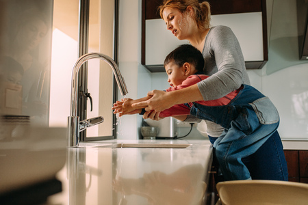Cute son washing hands with mother in the sink after cooking. Woman helping little boy to wash hands at kitchen sink. 스톡 콘텐츠