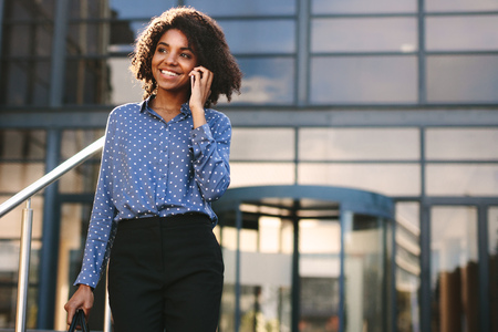 Smiling businesswoman talking over mobile phone while walking outside office building. Woman in formalwear walking outdoors and talking on phone.